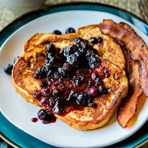 A plate of food, with bacon and French toast