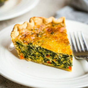 A piece of spinach quiche on a plate