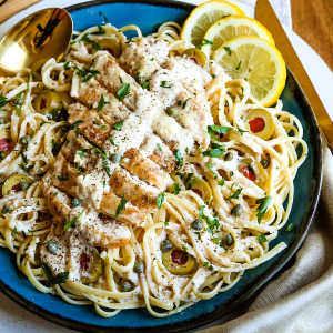 A bowl of food on a plate, with Chicken and Pasta