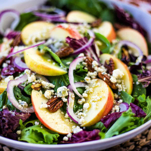 A bowl of salad, with apples and pecans