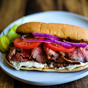 A sandwich on a plate, with sliced beef