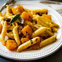 Butternut Squash Italian Sausage Pasta Bake on a white plate with fork