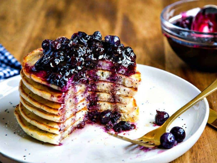 Stack of Lemon Poppy Seed Pancakes with Blueberry Compote on a white plate with fork