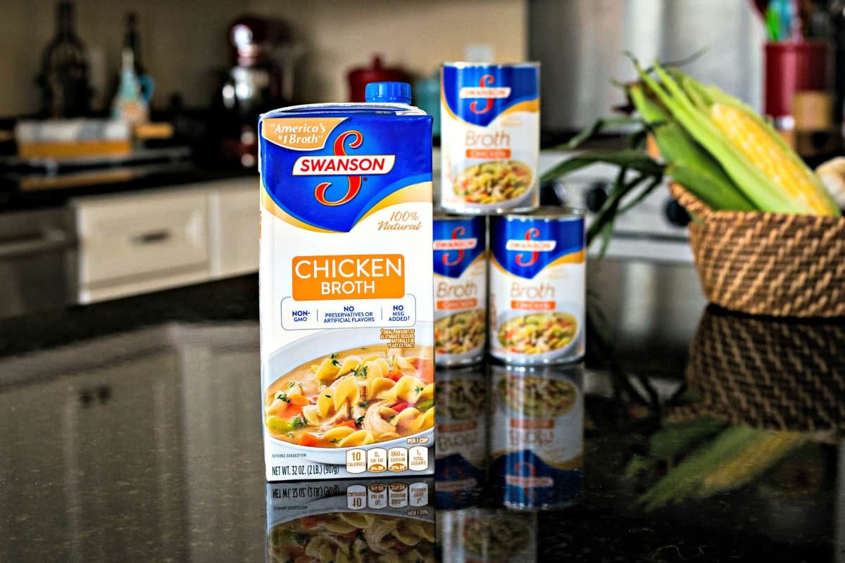 Swanson Chicken Broth in carton and cans on kitchen counter