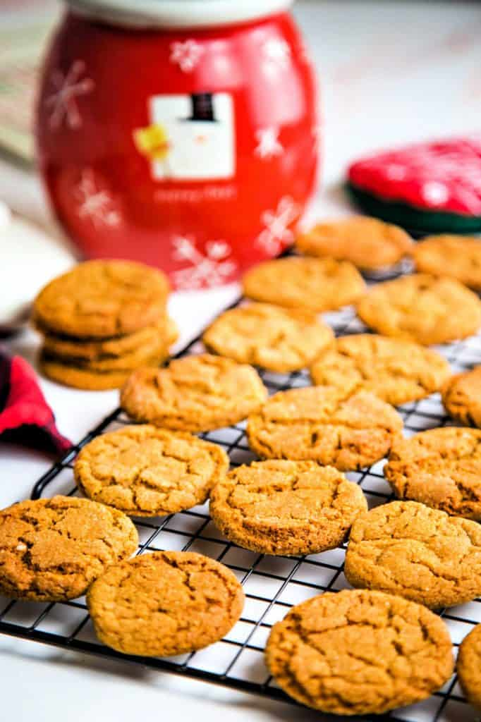 cookies on a cooling rack with a snowman cookie jar in the background