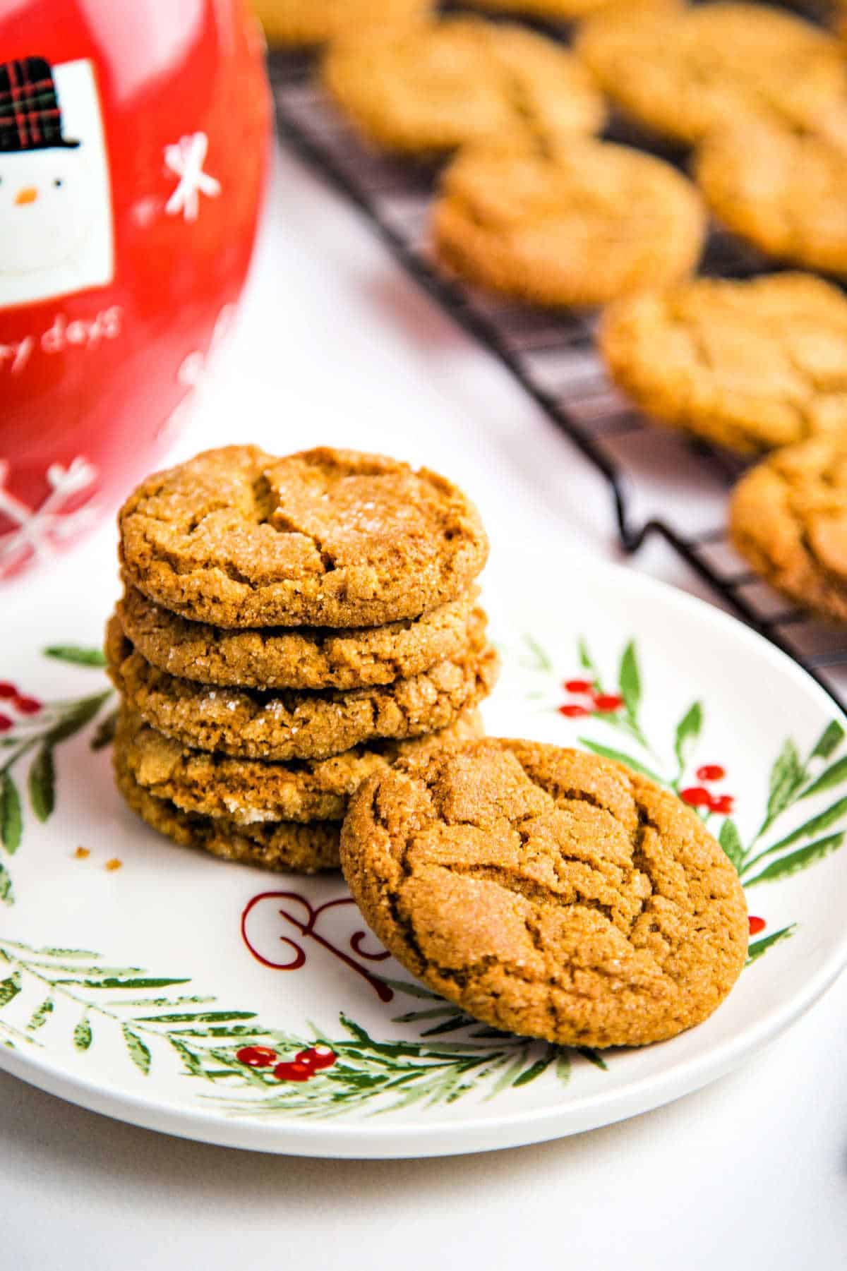 ginger cookies on a baking rack with a plate with a stack of cookies