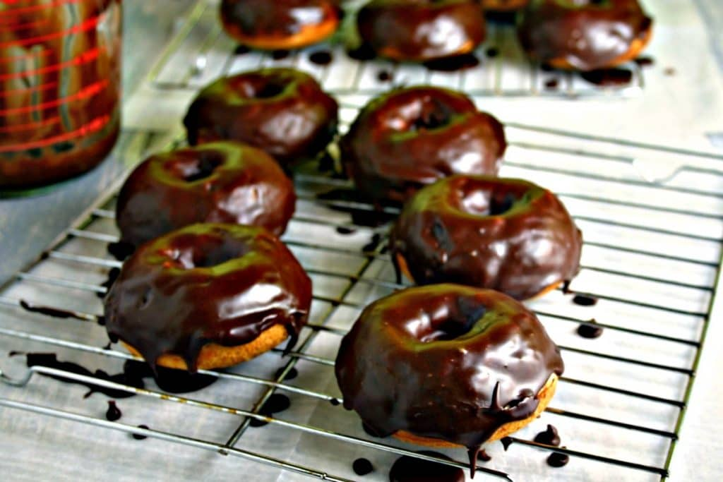 A doughnut sitting on top of a metal rack, with Mocha Glazed Baked Donuts