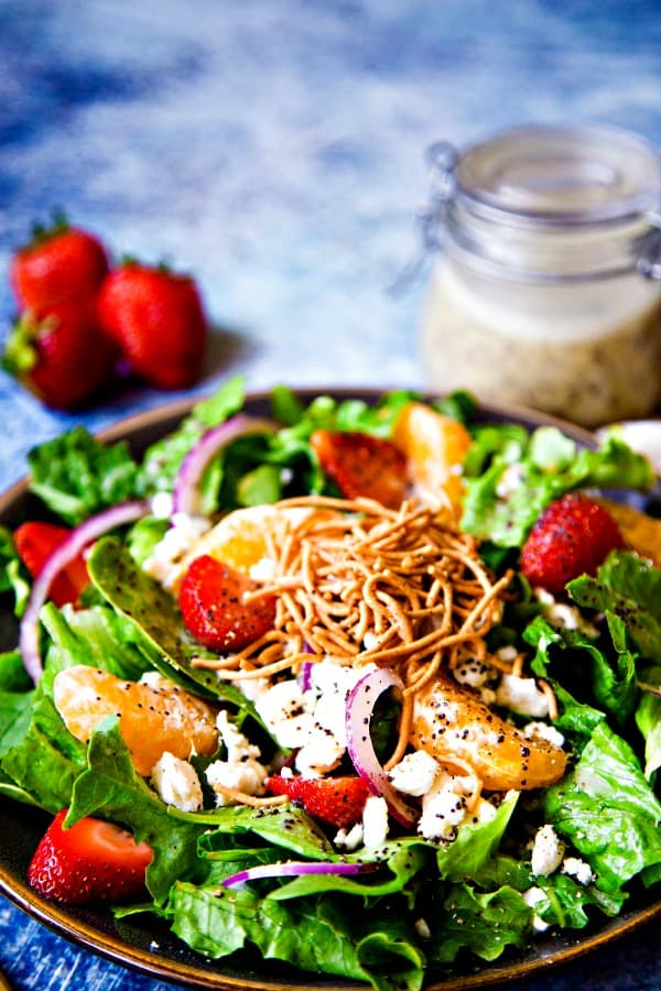 strawberry salad with poppy seed dressing garnished with rice noodles