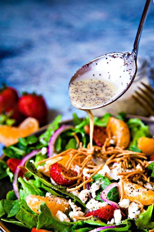 poppy seed dressing being drizzled from a spoon onto a salad