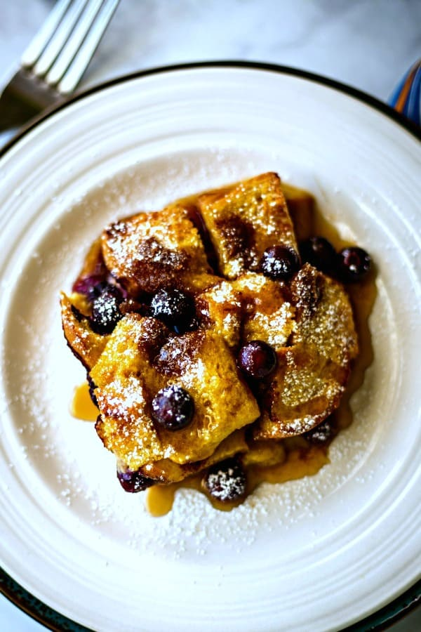 baked blueberry French toast with maple syrup on a white plate dusted with powdered sugar