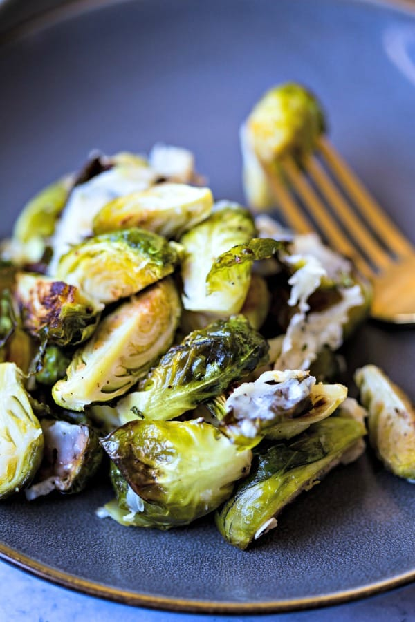 Brussels Sprouts with Asiago cheese on plate with gold fork