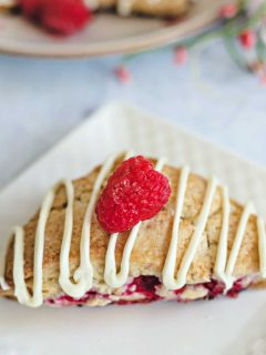 a raspberry scone with white chocolate drizzle on a white plate on a table