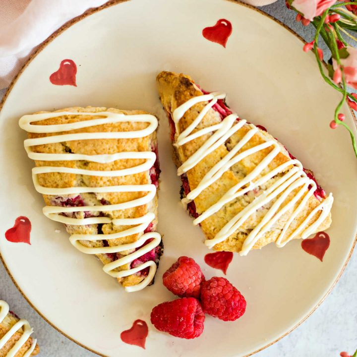raspberry scones on a Valentine heart plate with roses o a table