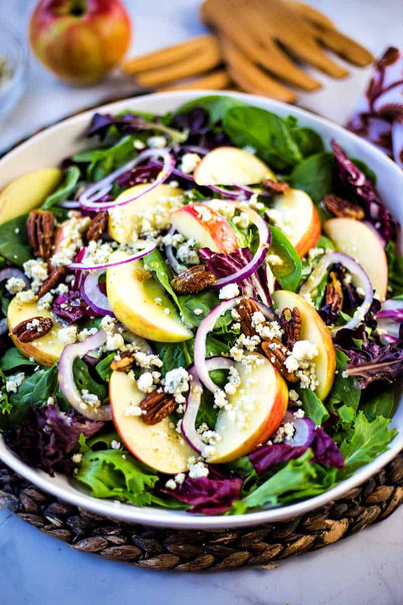 a white bowl with mixed salad greens, apple slices, red onions, and pecans