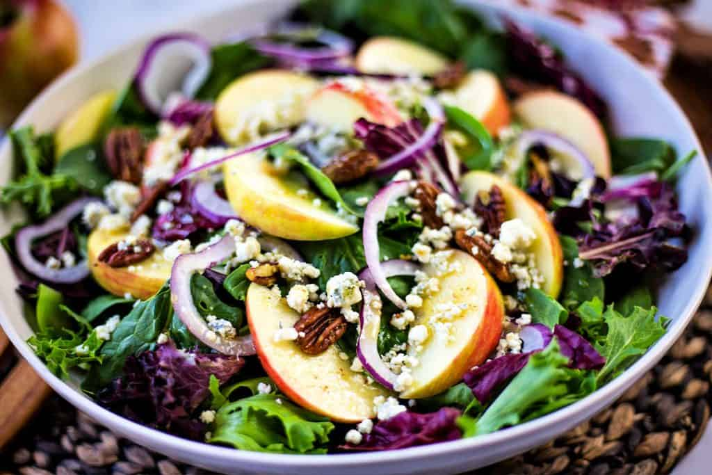 a bowl of salad with apple slices and pecans