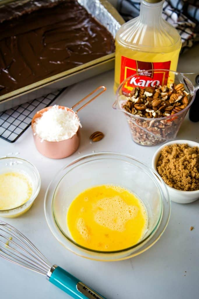 A table topped with bowls of food, ingredients for German Chocolate Pecan Pie Bars