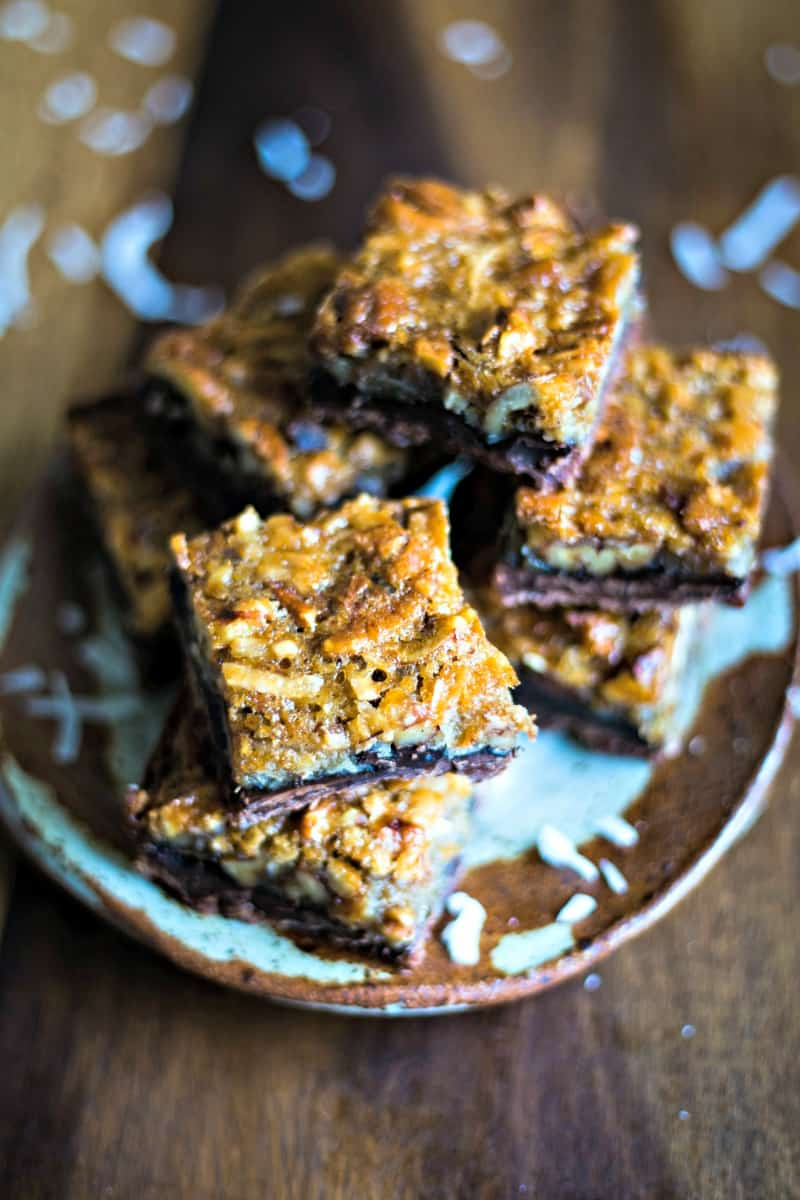 a stack of coconut pecan pie bars on a stone plate