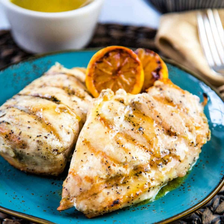 two grilled chicken breasts garnished with charred lemons on a blue plate