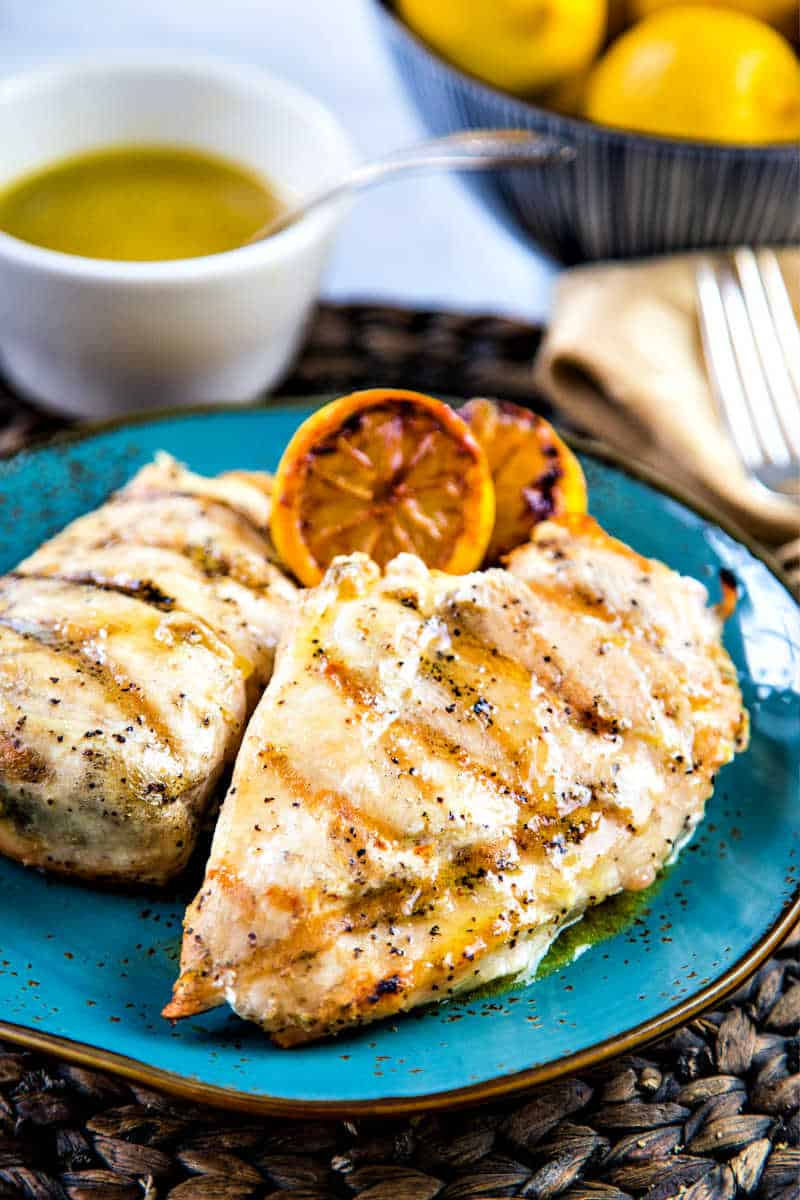 two grilled chicken breasts on a blue plate with lemons