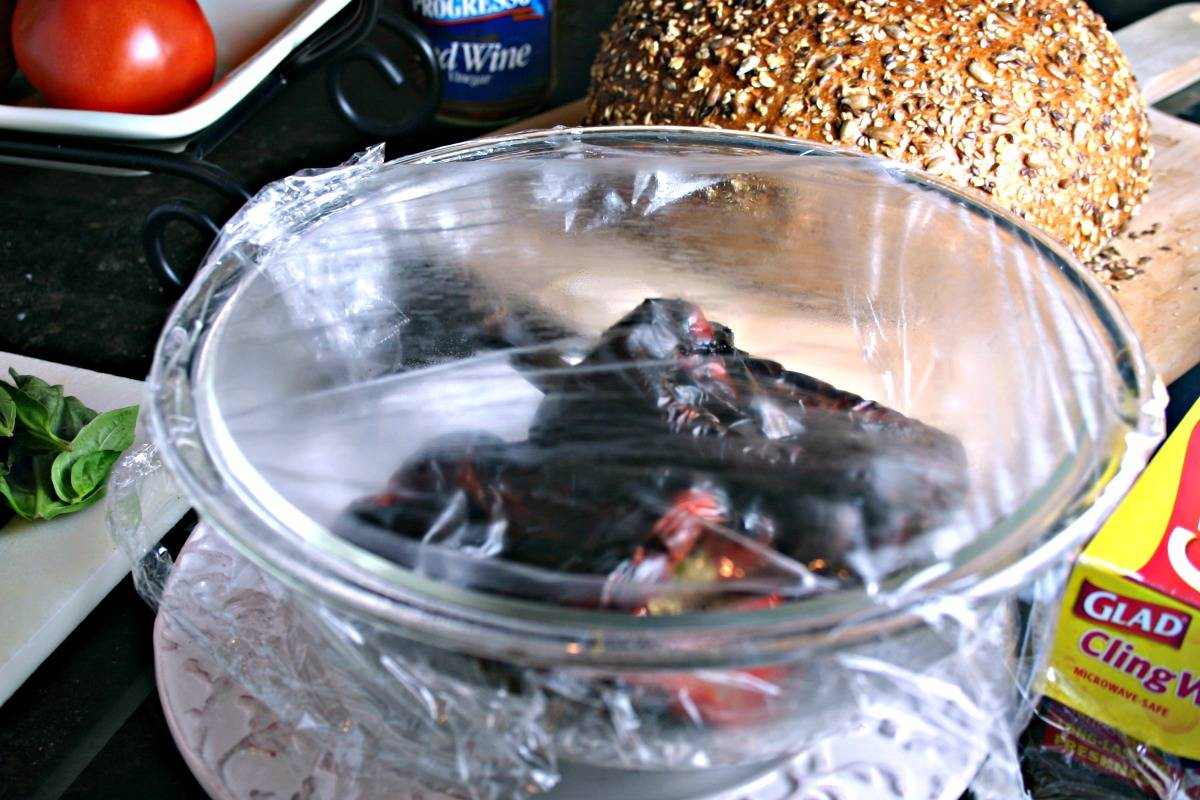 A bowl of roasted red bell peppers covered with plastic wrap