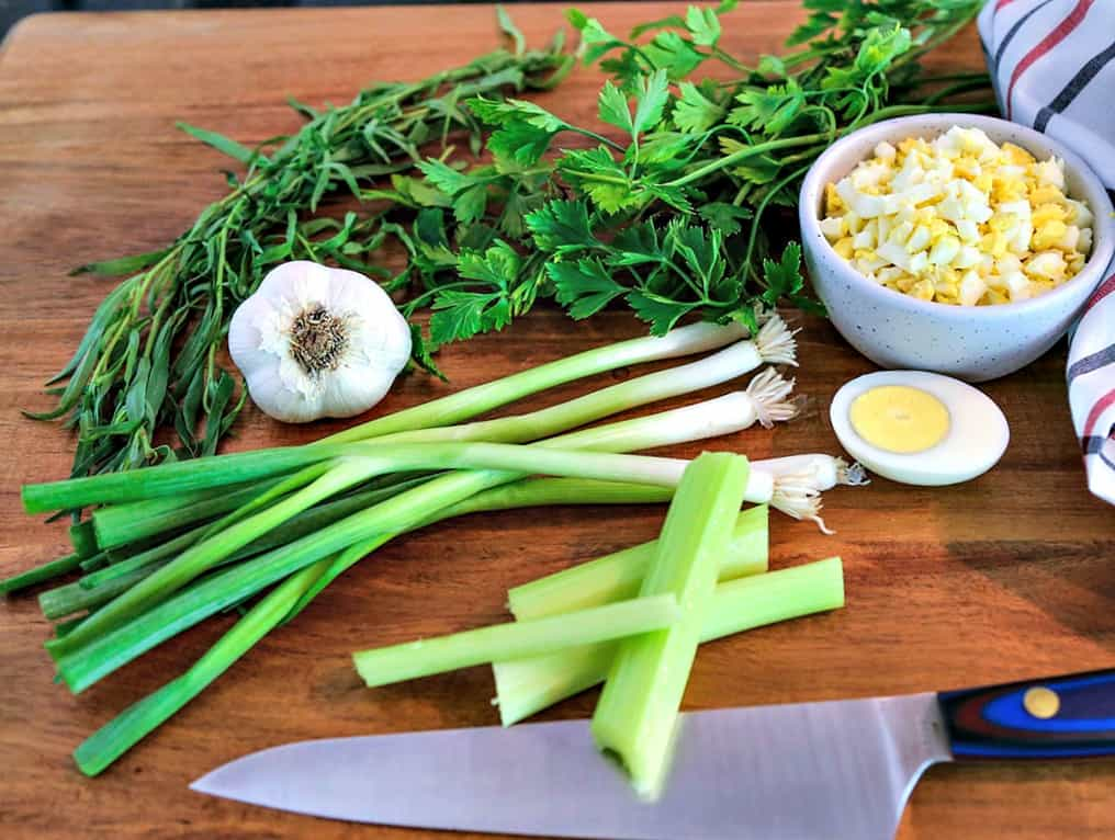 Green onions, celery, garlic, and boiled eggs on top of a wooden cutting board
