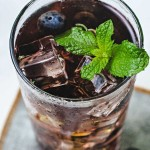 a glass of blueberry tea with ice cubes and a mint sprig garnish sitting on a coaster.