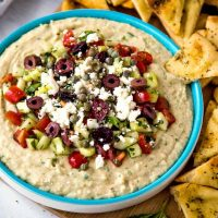 Mediterranean Layered Dip with pita triangles on a wooden board
