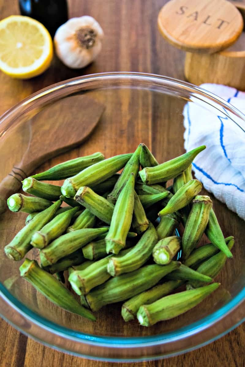 a glass bowl of raw okra pods