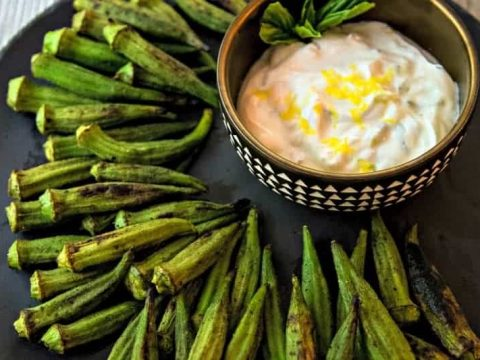 whole okra with char marks on a plate with a lemon dipping sauce