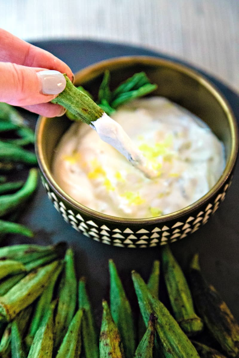 dipping okra in a bowl of lemon basil greek yogurt