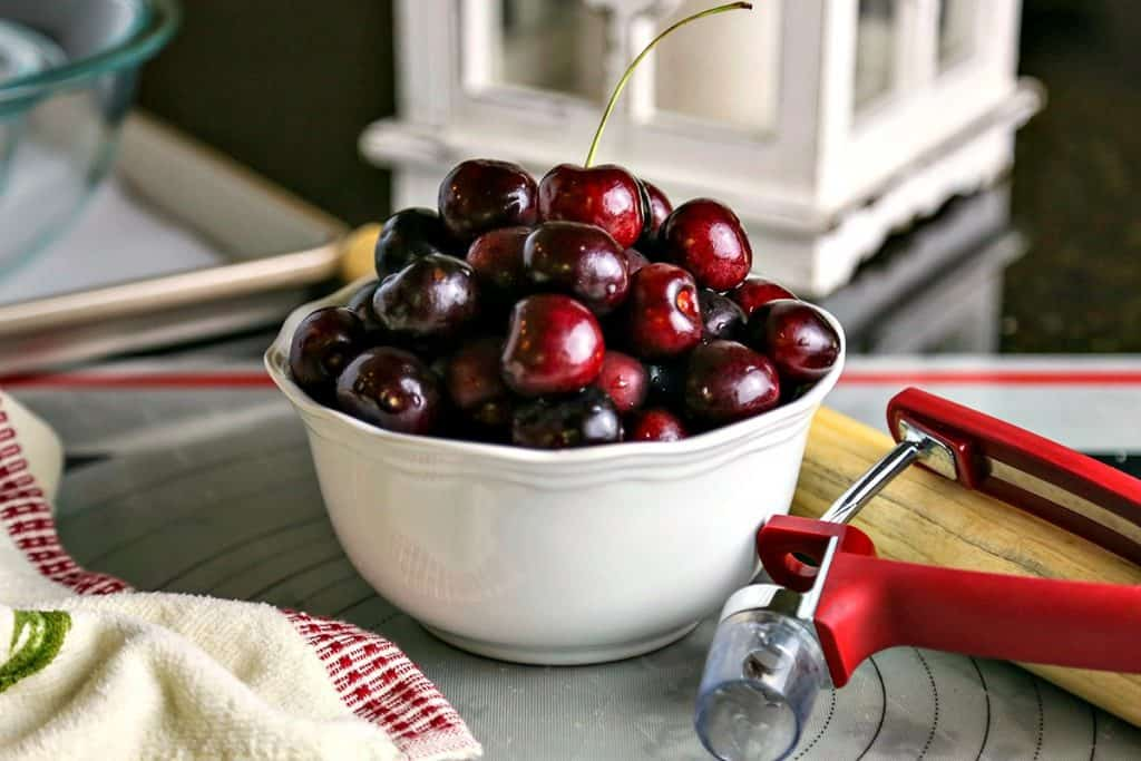 bowl of cherries with a cherry pitter
