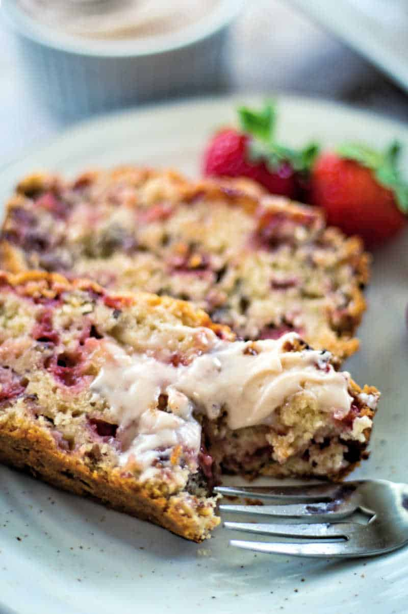 slices of strawberry bread on a plate with a fork and a smear of butter