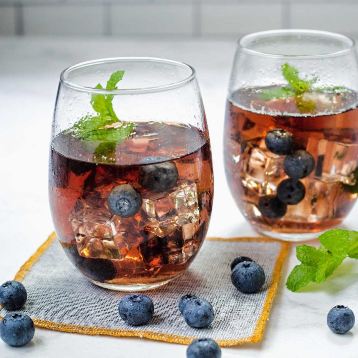 two glasses of blueberry tea with blueberries and mint springs on a counter.