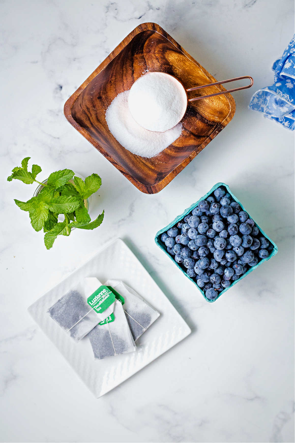 ingredients for blueberry tea on a table: blueberries, sugar, tea bags, and mint sprigs.