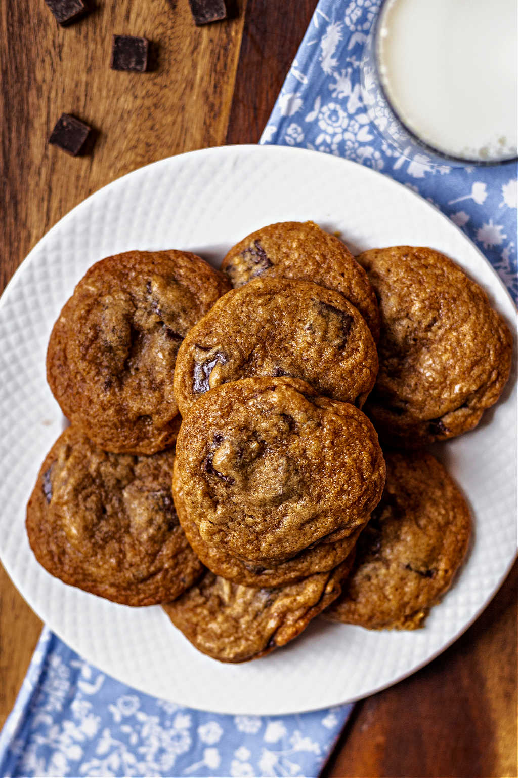 chocolate chunk cookies on a white plate on a wooden table.