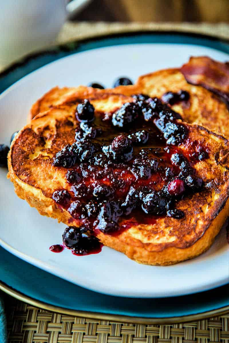 two slices of french toast on a white plate with a blueberry compote