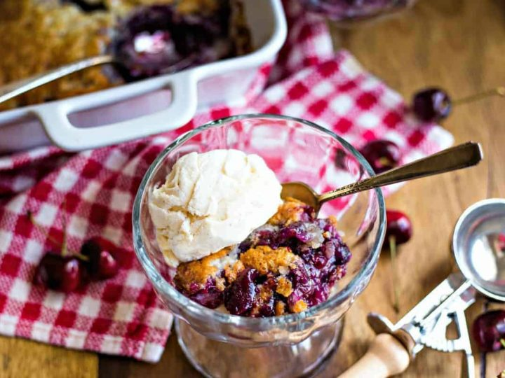 a bowl of cherry cobbler with a scoop of ice cream on top