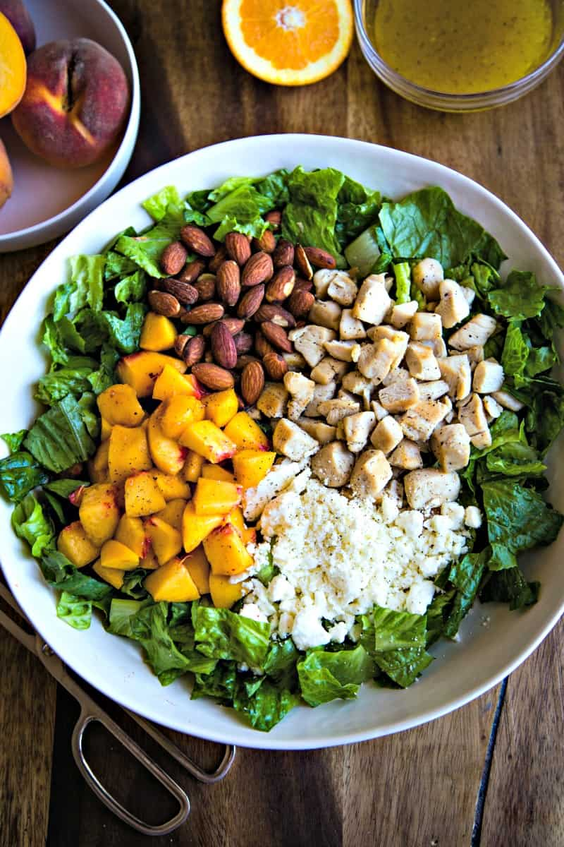 white bowl on a wood plank table with ingredients for chopped chicken and peach salad