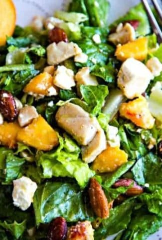 A plate of salad and a fork, with Peaches and Chicken