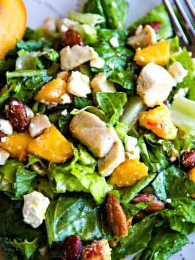 green salad with peaches, almonds, and feta cheese on a plate with fork
