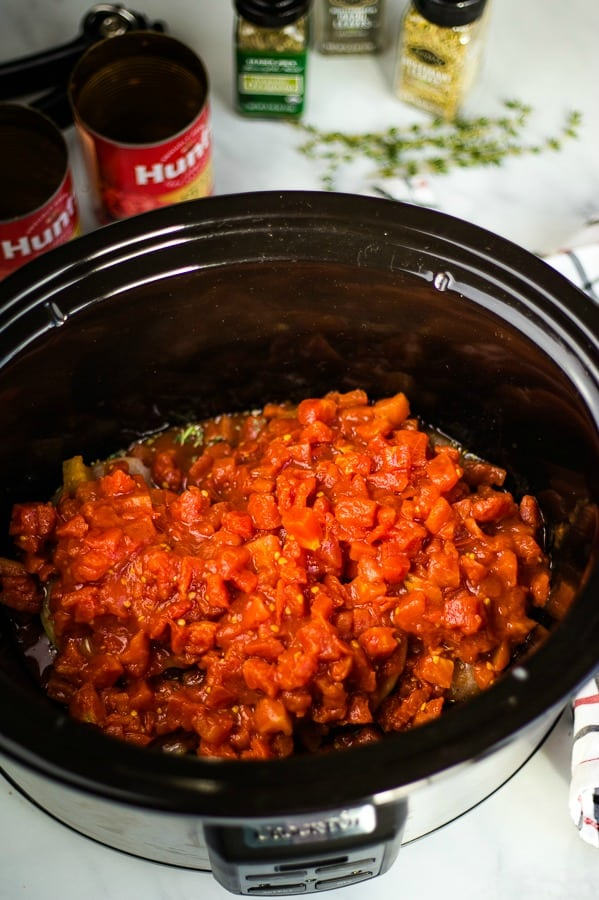 petite diced tomatoes on top of raw chicken in crockpot