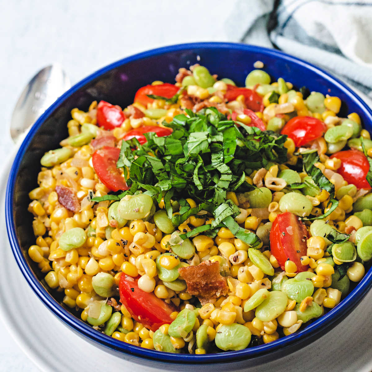 corn succotash garnished with a mound of basil chiffonade in a blue bowl on top of a white plate.