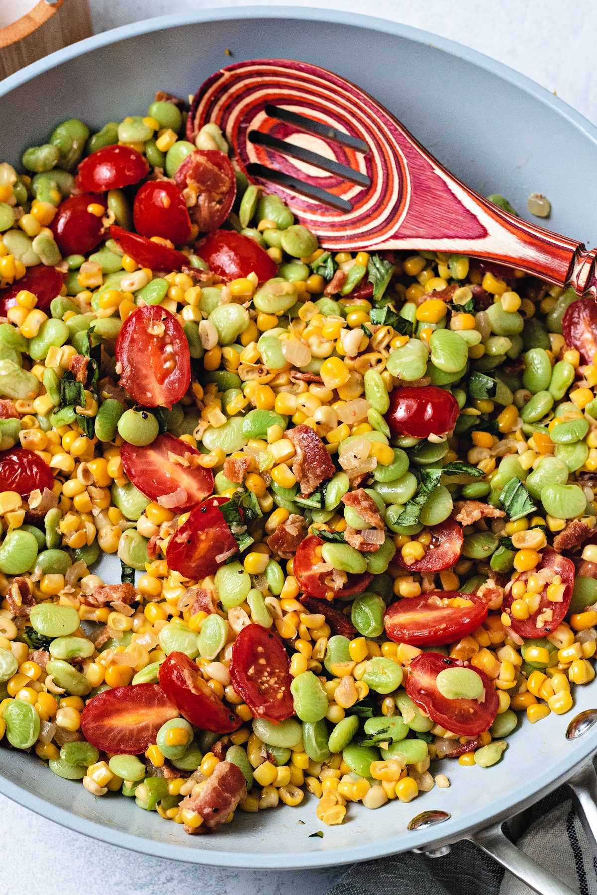 corn succotash with tomatoes and basil in a frying pan with a spoon.