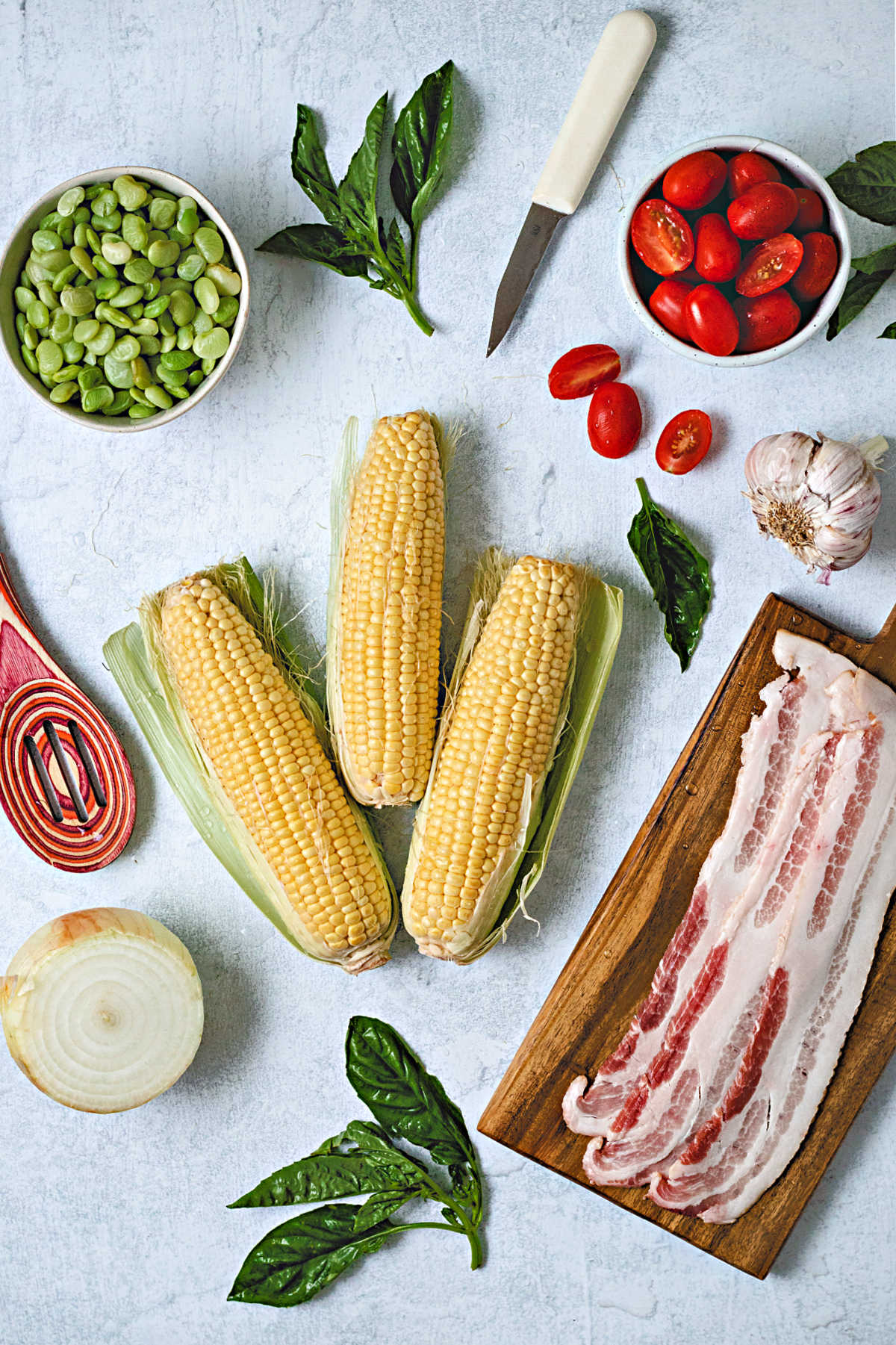 ingredients for corn succotash on a table: 3 ears of corn, fresh basil, a bowl of lima beans, grape tomatoes, onion, garlic, and bacon slices.