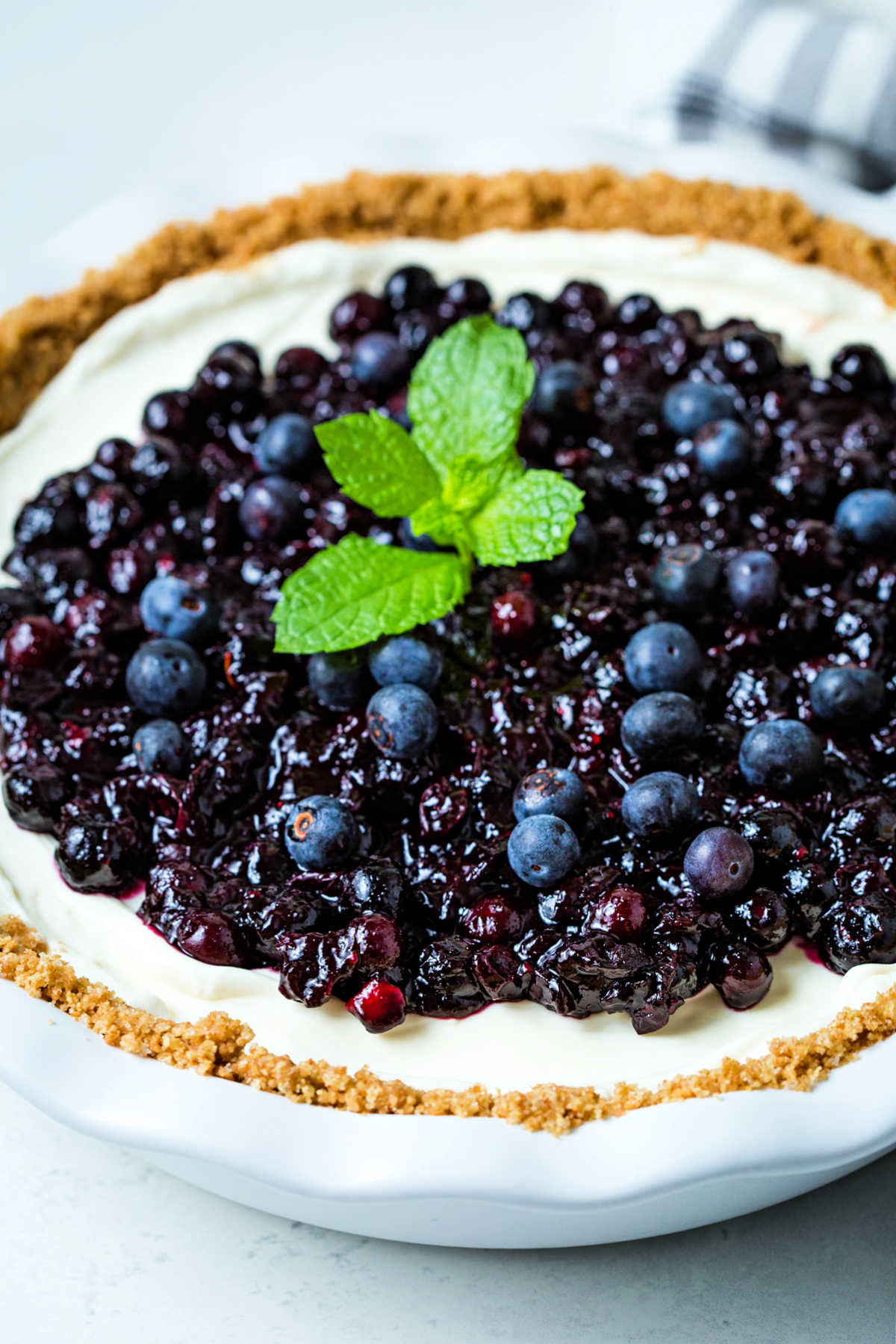 a no bake blueberry cheesecake in a white pie plate with a mint sprig garnish.