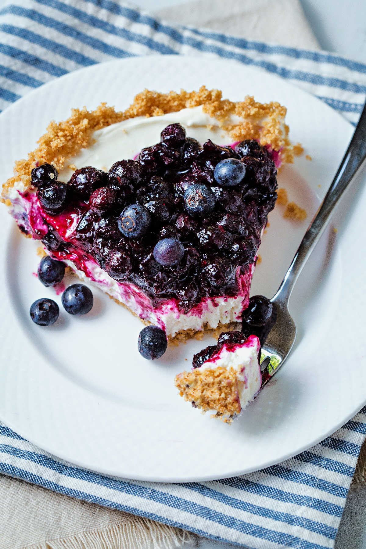 a bite of no bake blueberry cheesecake on a fork alongside a slice on a white plate.