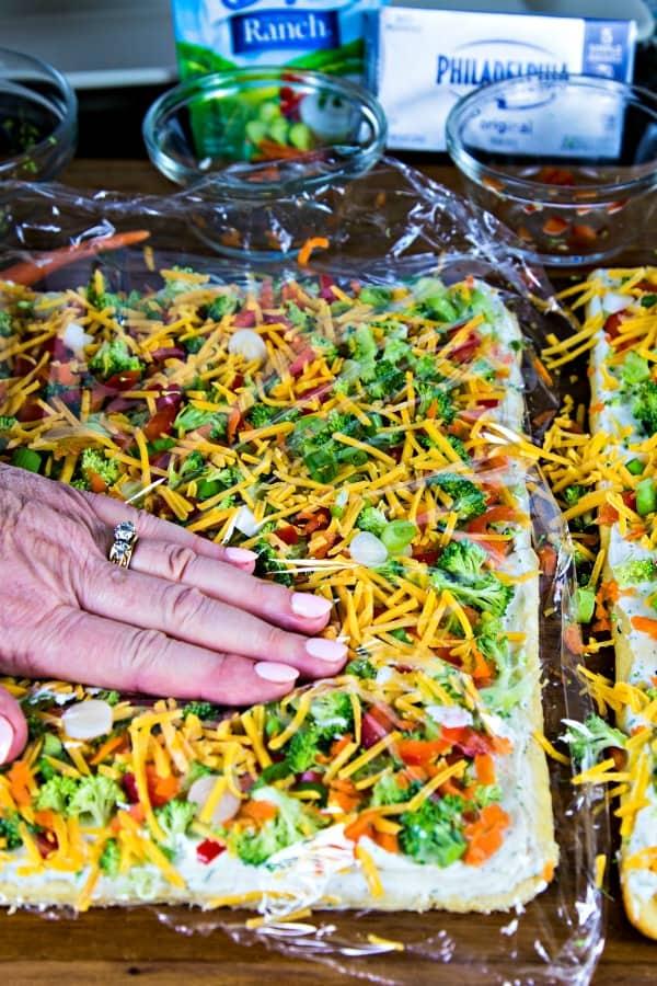 Use plastic wrap to press veggies into the cream cheese on cool veggie pizza