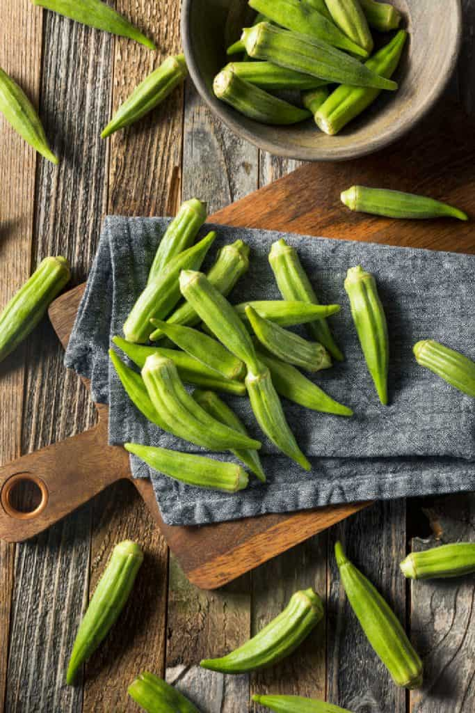 whole pods of fresh okra on a wooden cutting board