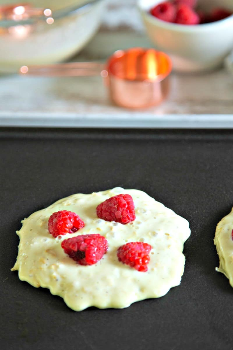 pancakes cooking on an electric griddle with raspberries on top