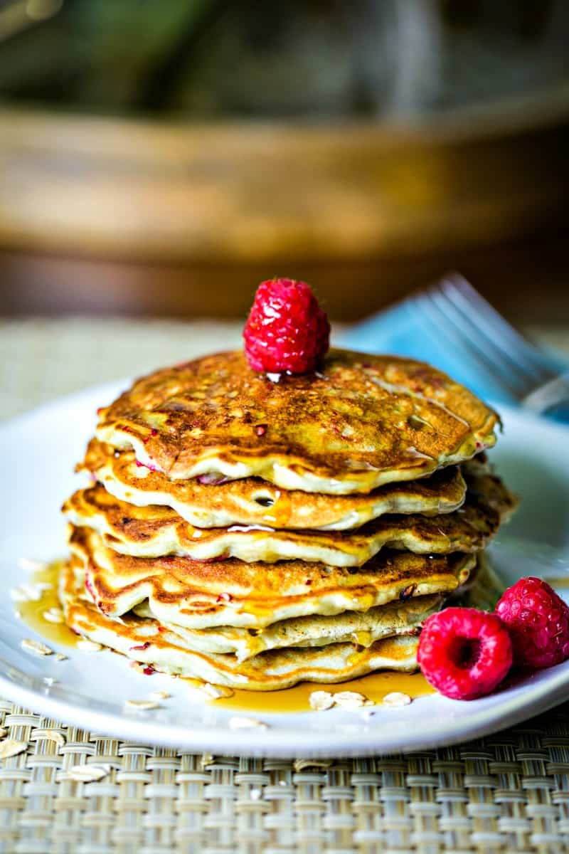 stack of pancakes on white plate with raspberries